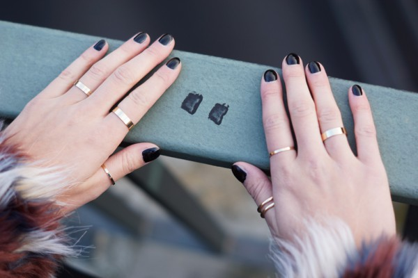 golden rings and black nail polish