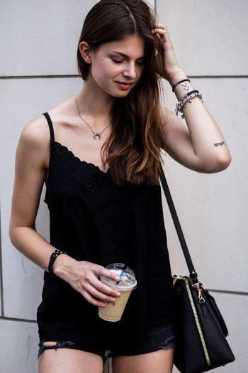 Komplett schwarzes Outfit und ein Iced Coffee