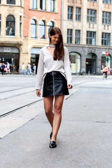 Combining a knitted pullover with a faux leather skirt
