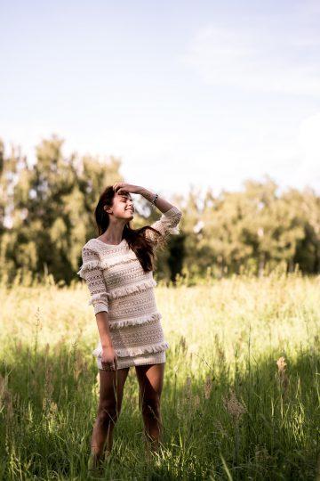 Wearing a beige fringe dress in the fields
