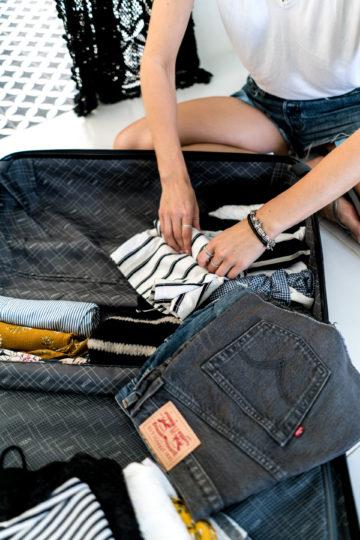 Kleidung zusammenrollen im Koffer