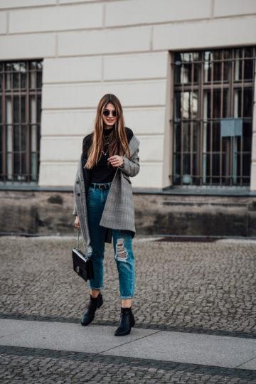 Karierter Mantel kombiniert mit einem schwarzen Rollkragenpullover