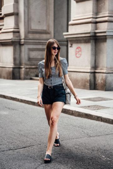 Reiseoutfit: Gingham Bluse und schwarze Jeansshorts kombiniert